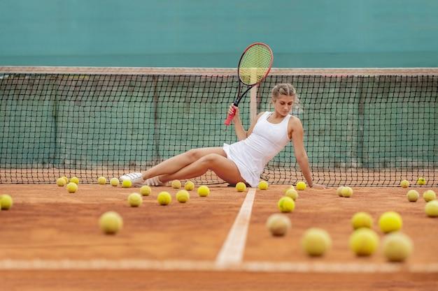 Mujer de jugador de tenis profesional con raqueta y pelota cerca de la red en la cancha.