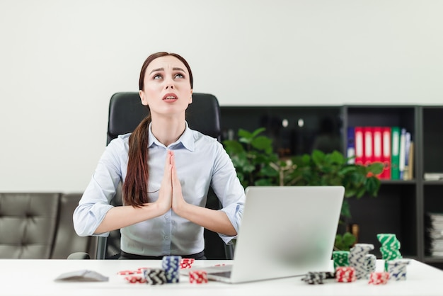 Mujer jugando al casino y al póquer en línea a través de una computadora portátil en la oficina y rezando para ganar