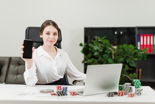 Mujer jugando al casino en línea y al póker a través de una computadora portátil en la oficina y mostrando la pantalla del teléfono en blanco