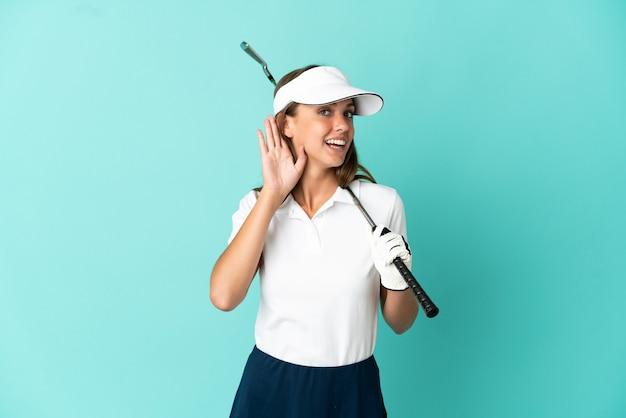 Mujer jugando al golf sobre fondo azul aislado escuchando algo poniendo la mano en la oreja