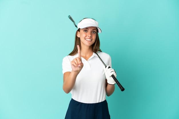 Mujer jugando al golf sobre fondo azul aislado mostrando y levantando un dedo