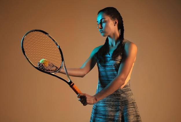 Mujer jugando al tenis aislado en la pared marrón