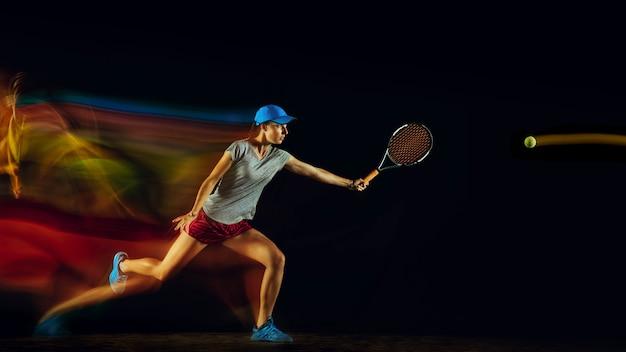 Una mujer jugando al tenis aislado en la pared negra en luz mixta y stobe