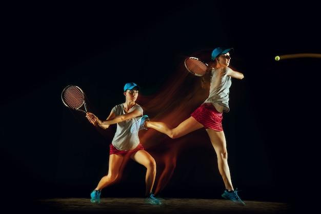 Una mujer jugando al tenis en diferentes posiciones aislado en la pared negra en luz mixta y stobe