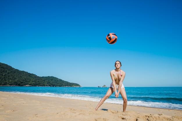 Mujer jugando al voleibol de playa en la orilla