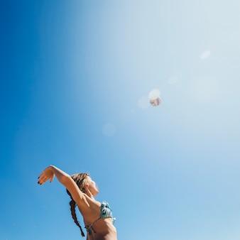 Mujer jugando al voleibol de playa con sol de fondo