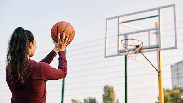 Mujer jugando baloncesto sola con espacio de copia
