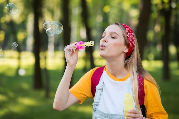 Mujer jugando con burbujas al aire libre