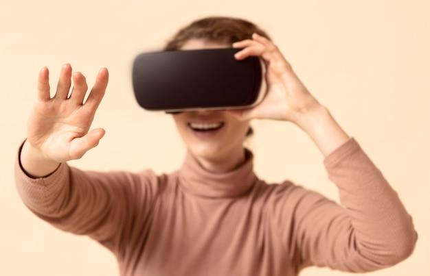 Mujer jugando con casco de realidad virtual y alcanzando su brazo