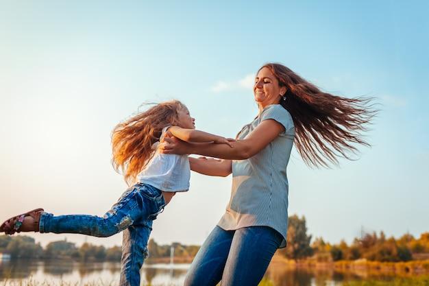 Mujer jugando y divirtiéndose con el niño por el río de verano.