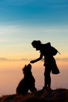 Mujer jugando y entrenando con su perro pastor hace tiempo para ver una galleta