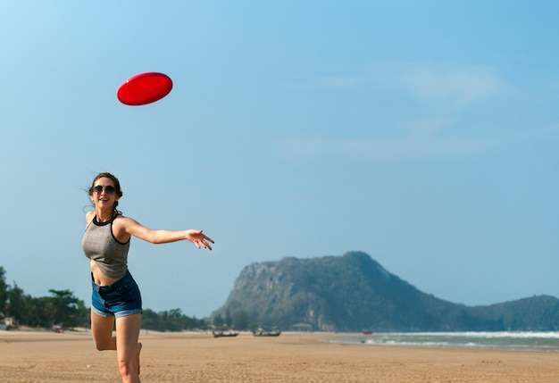 Una mujer está jugando frisbee en la playa