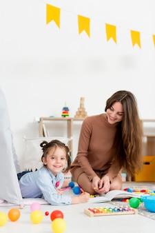 Mujer jugando con niña y juguetes en casa