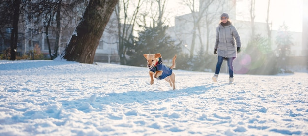 Mujer jugando con perro en la nieve.