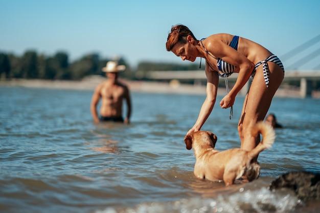 Mujer jugando con un perro en el río