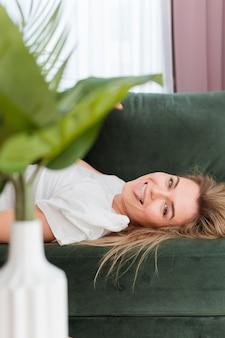 Mujer jugando y planta de primer plano