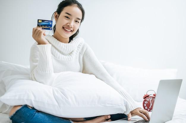 Mujer jugando portátil y mantenga una tarjeta de crédito.