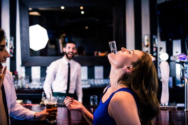 Mujer jugando con su disparo en un bar con amigos