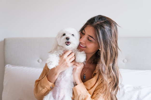 Mujer jugando con su perro en casa