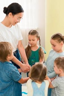 Mujer jugando con sus alumnos durante lass en interiores