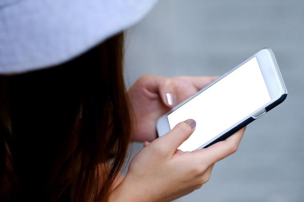 Mujer está jugando un teléfono inteligente de pantalla blanca.