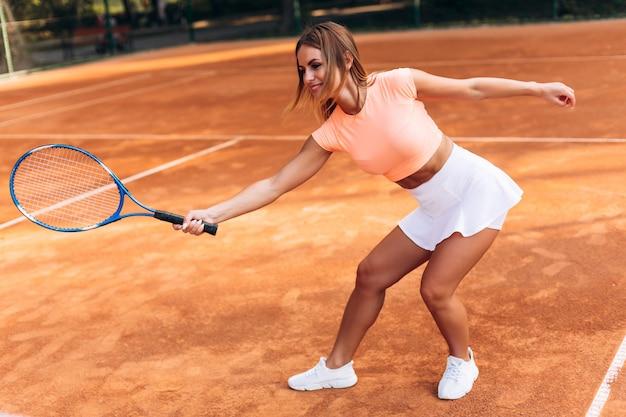Mujer jugando tenis en la cancha y sosteniendo la raqueta