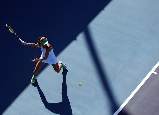 Mujer jugando tenis golpeando la pelota