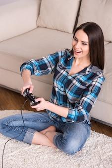 Mujer está jugando videojuegos, sentada en el suelo en casa.