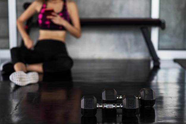 Mujer jugar teléfono inteligente después de entrenamiento con mancuernas