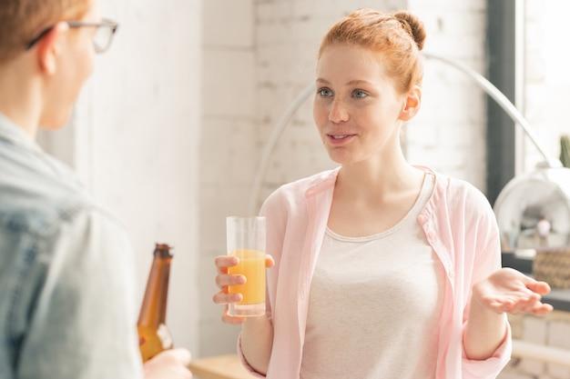 Mujer con jugo y hombre con cerveza hablando en fiesta