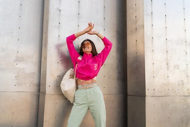 Mujer juguetona divirtiéndose en chaqueta rosa neón sobre muro urbano gris metálico