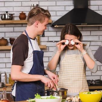 Mujer juguetona con hombre cocinando en cocina