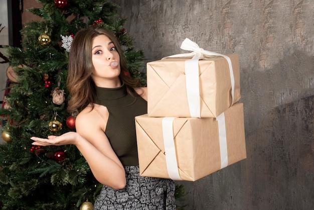 Mujer juguetona posando con regalos de navidad delante de pinetree