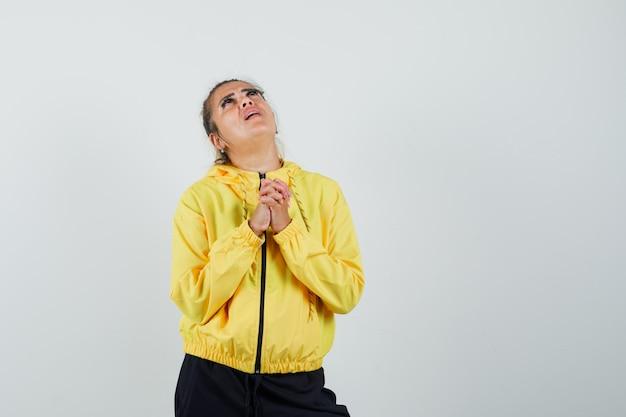 Mujer juntando las manos en gesto de oración en traje deportivo y mirando esperanzado. vista frontal.