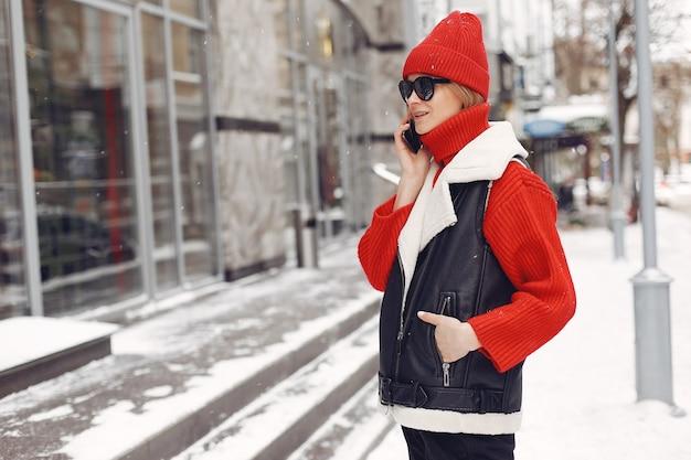 Mujer junto al edificio. estado de ánimo de año nuevo. dama de chaqueta negra.