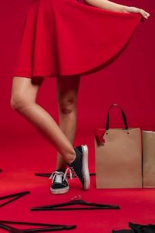 Mujer junto a bolsas de compras en el piso con fondo rojo.