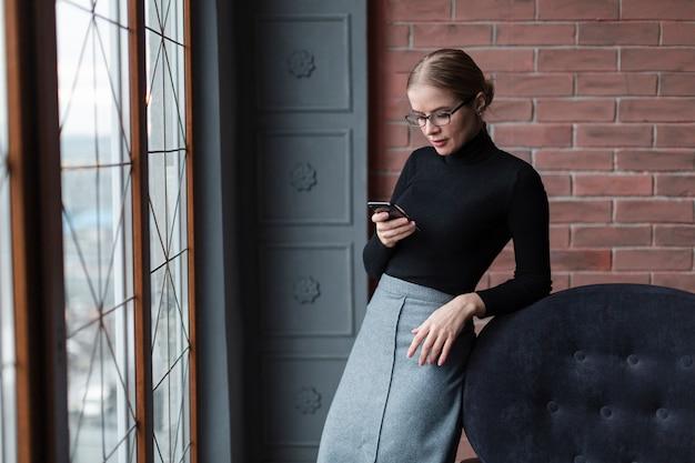Mujer junto a la ventana mediante dispositivo móvil