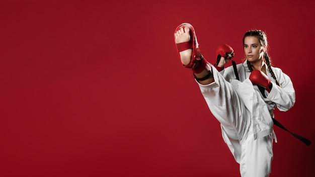 Mujer de karate en acción aislada en fondo rojo
