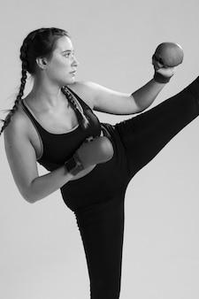 Mujer de karate blanco y negro pateando
