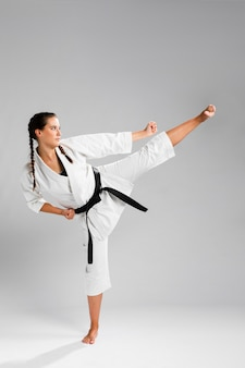 Mujer de karate de lado en kimono blanco tradicional sobre fondo blanco.