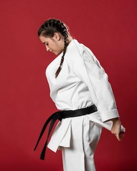 Mujer de karate de lado en kimono blanco tradicional sobre fondo rojo.