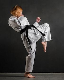 Mujer de karate practicando tiro completo