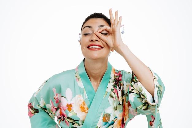 Mujer en kimono japonés tradicional haciendo bien firmar mirando a través de los dedos feliz y alegre sonriendo en blanco
