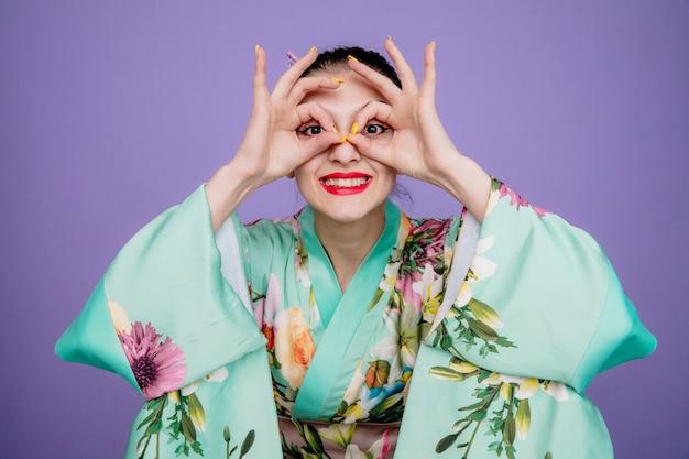 Mujer en kimono japonés tradicional haciendo gesto binocular a través de los dedos feliz y alegre en púrpura