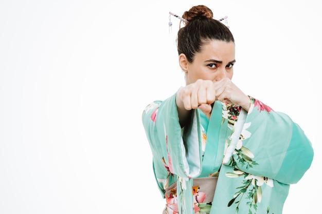 Mujer en kimono japonés tradicional con rostro serio mostrando puños posando como un luchador en blanco