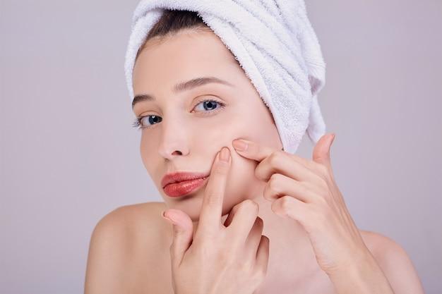 Una mujer con los labios carnosos se aprieta un grano en la mejilla.