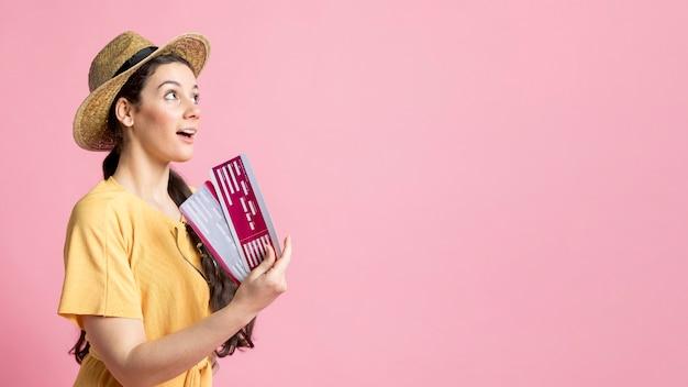 Mujer de lado con billetes de avión con espacio de copia