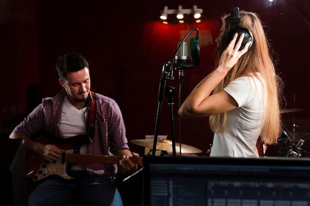 Mujer de lado cantando y chico sentado con una guitarra