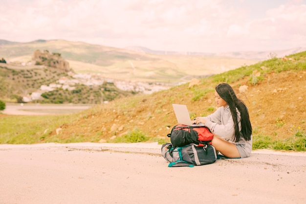 Mujer en el lado de la carretera y escribiendo en la computadora portátil en las mochilas