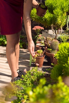 Mujer de lado cuidando sus plantas